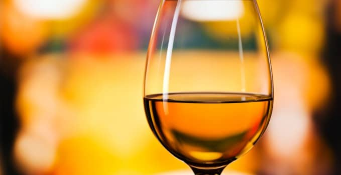 glass with white wine , focus on foreground