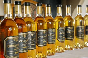 bouteilles de vin blanc alignées avec évolution de la couleur - chateau guiraud vin de garde